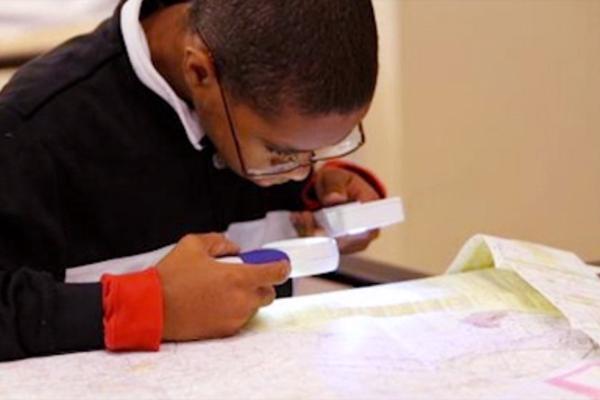 A student using a handheld magnifier and a light to read the small print on a map.