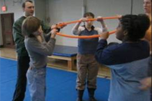 Students performing hula hoop exercise in adaptive physical education class.