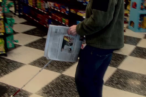 A young boy who is visually impaired uses a mobility cane and walks to  the counter to purchase a newspaper.