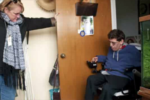 A oung man in a blue sweatshirt in a motorized wheelchair attempting to exit a small office.