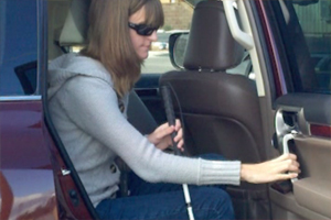 A teenaged girl wearing sunglasses and holding a cane, getting out of an SUV.