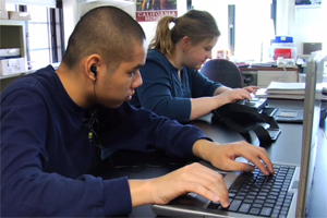 In a science class, two students who are blind take notes on his laptop and on her electronic braille notetaker.