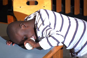 The visually impaired boy rests his head and upper body on a desk while holding a plastic shaker in his hand.