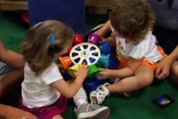 Two young girls who are visually impaired and multiply disabled are engaged in mutual play.