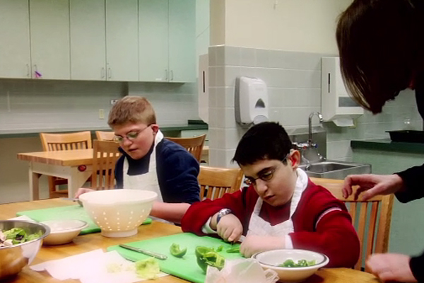 A group of students who are deaf-blind are being supervised as they prepare a lunch.