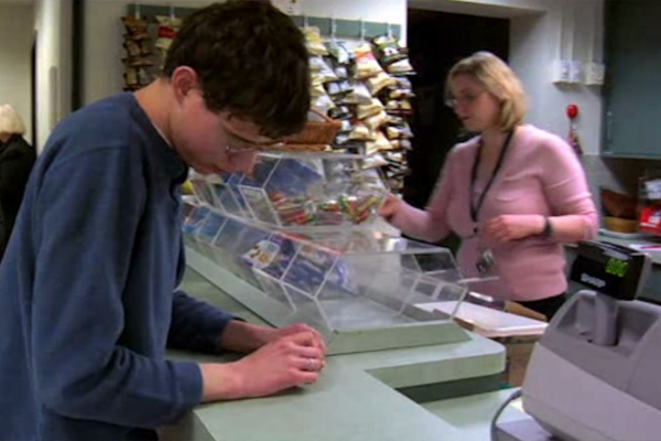 A young male who is blind attempting to purchase a fruit snack in the student café.