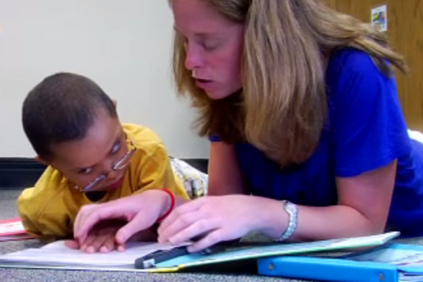 A teacher and a young boy who is visually impaired are reading a book together.