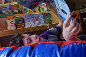A dark haired boy reclines on a bean bag chair and turns the pages of a book.