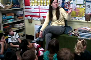 A female teacher reads a storybook to a classroom of children.