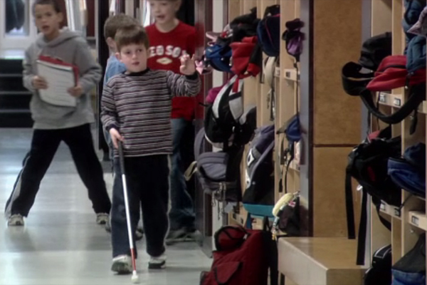 A blind boy navigates the hallway with his cane.
