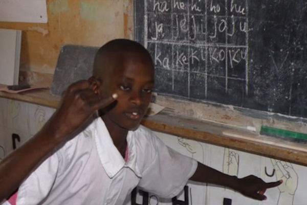 In a classroom in Africa, a young boy points to a diagram that describes how to sign the letter J.