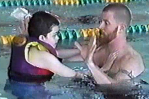 A young boy who is visually impaired exercising in the pool with a teacher.