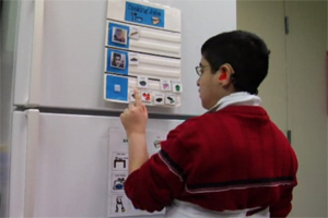 A dark haired boy in a red sweater stands in front of the refrigerator.