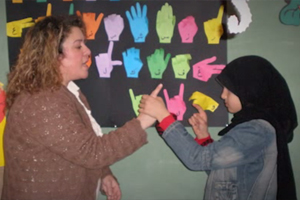 A young and blind Lebanese girl learns how to communicate using tactile signing.