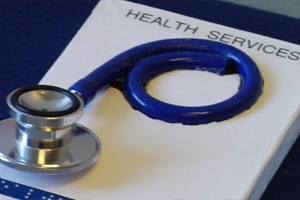"A tangible symbol card labeled ""health services"" that has part of a stethoscope and tubing attached."