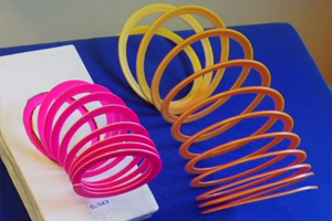 A tangible symbol card with a few coils of a plastic slinky toy attached is displayed on a blue board.