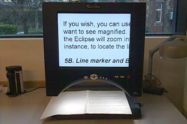 An open binder beneath a text magnifying device.
