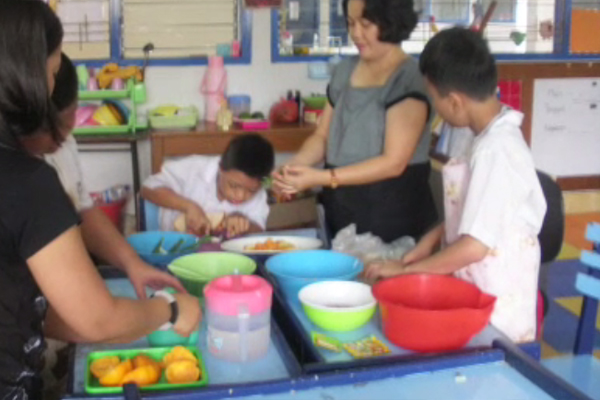 Three MDVI students and two teachers working in the kitchen area of a school.