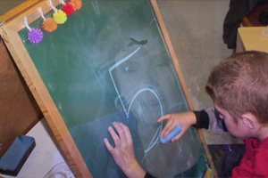 A young boy writes the number five on the board.