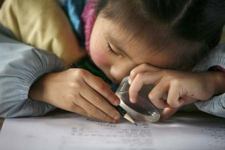 A young girl is using a magnifying device to aid her do homework.
