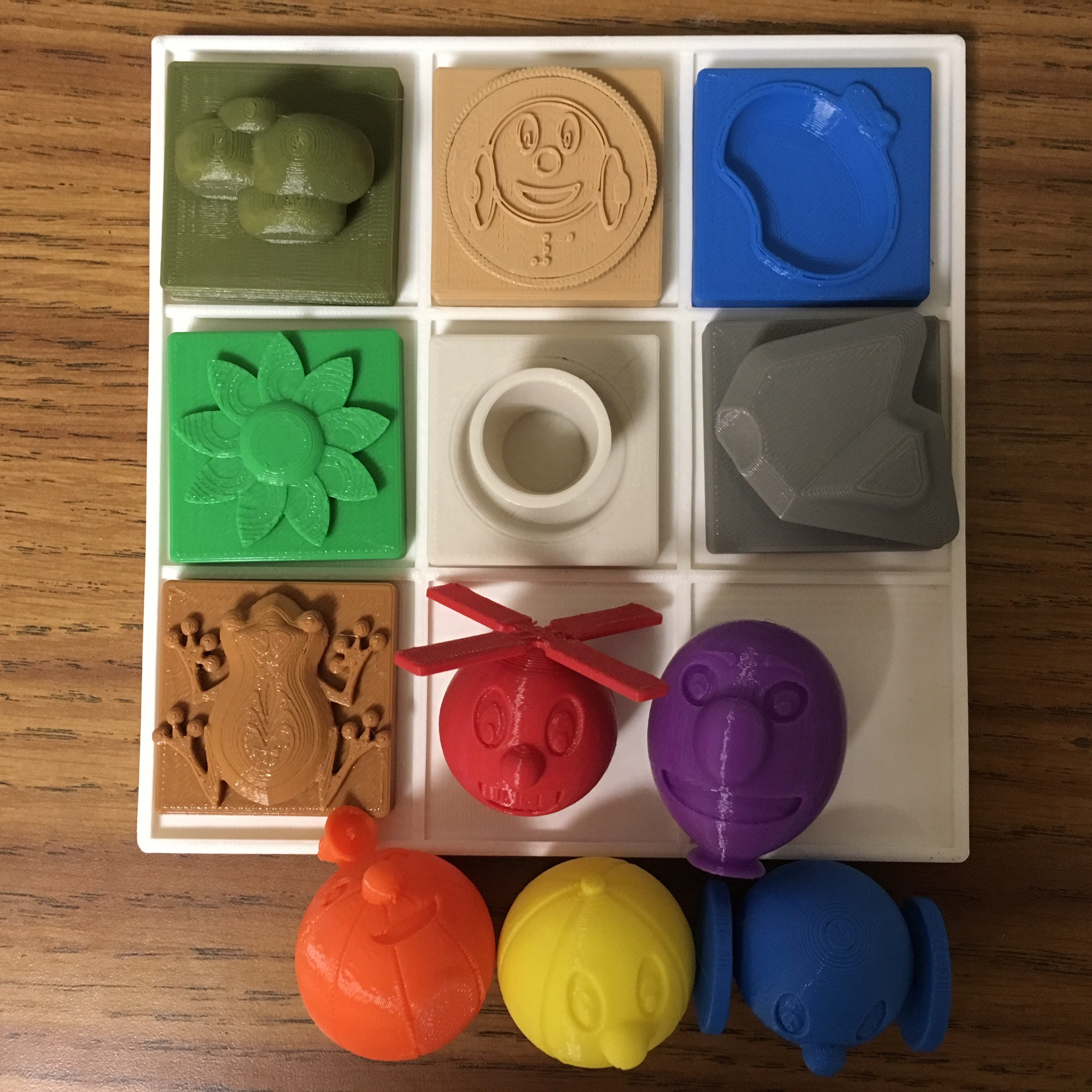 Photo of Ballyland 3D printed characters, obstacles and grid - each printed in a solid bright color.