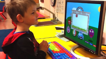 Photo of a young boy with a large print colorful keyboard intently watching the computer monitor while playing Ballyland Keyboarding.