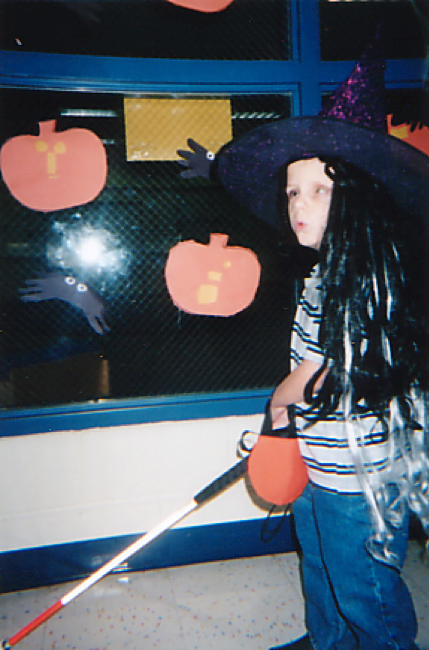 5-year old boy wearing a witch's wig and pointing hat holding a small pumpkin bag while using his cane traveling down a school hallway making scary sounds.