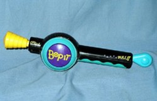 Original physical Bop-It game with a long handle with different ends that twist and a circular area in the middle.