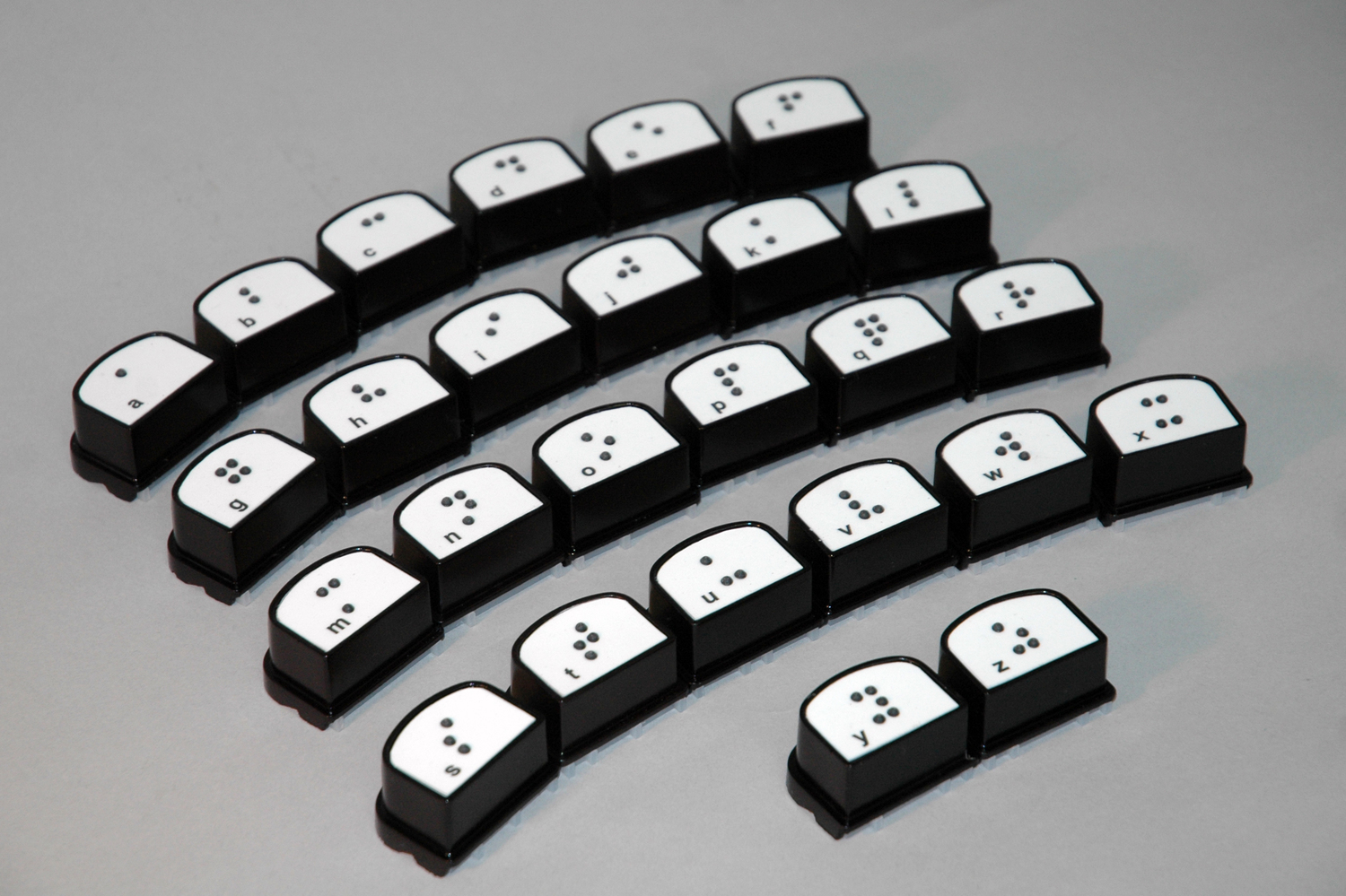 Photo of BrailleBlox: individual white blocks each with a black braille letter in the center and the corresponding print letter in the bottom left corner.