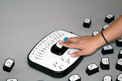 Photo of the full BrailleBot game: Braille alphabet on the base game with the braille letter P being inserted into the window in the center of the base game.