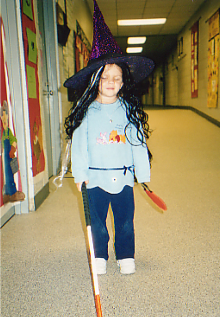 5 year old girl dressed with long black and white hair and pointy witches hat carrying a small bag while traveling with her cane in a school hallway.