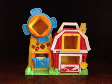 Photo of a colorful barn shape sorter with a high contrast black background