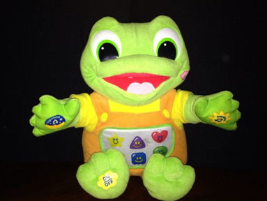 photo of a colorful plush toy frog with various buttons on his chest, hands and feet; background is high contrast black.