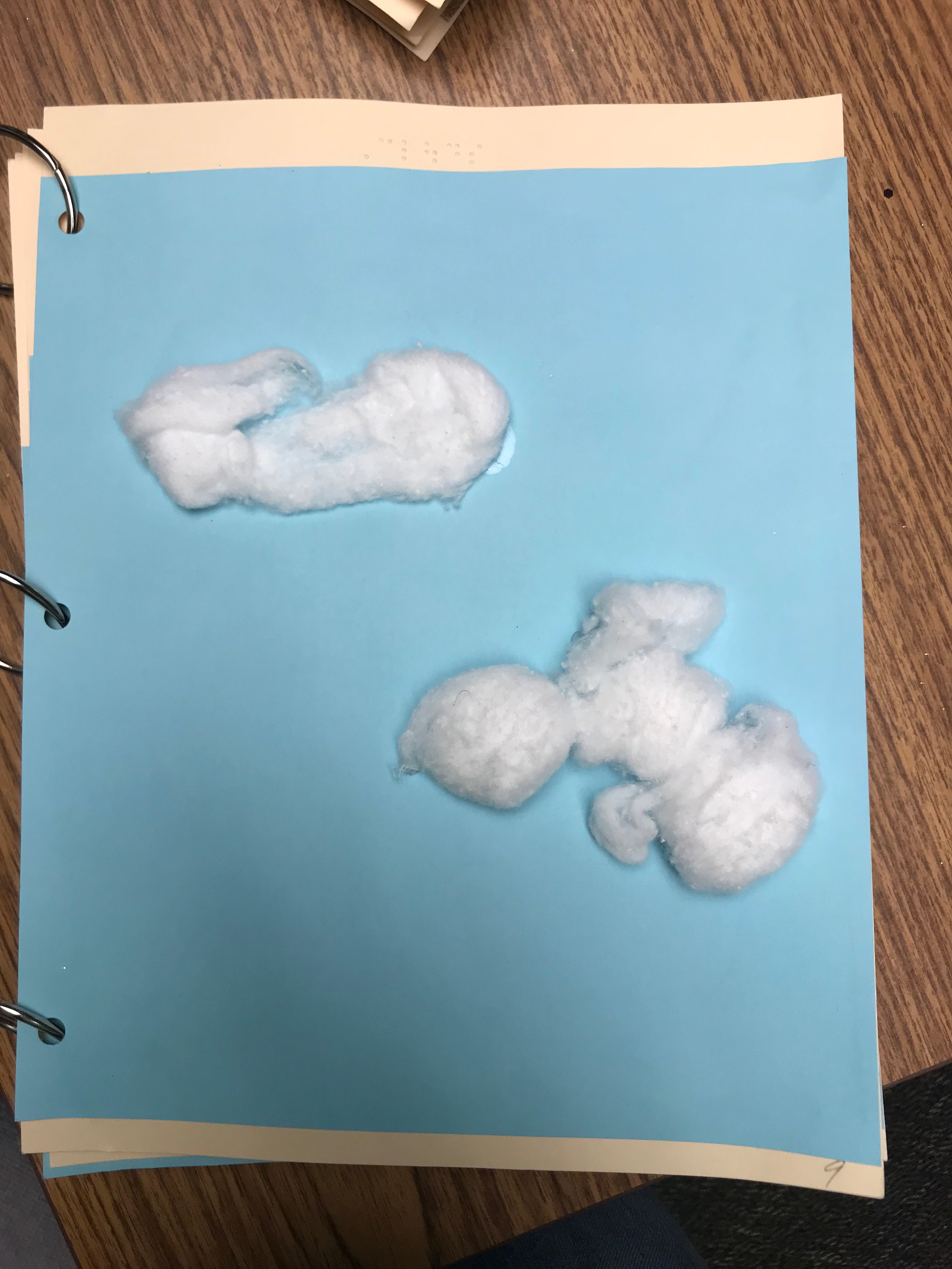 Photo of Cloud Title page with the brailled text 'Clouds' and cotton balls representing the clouds.
