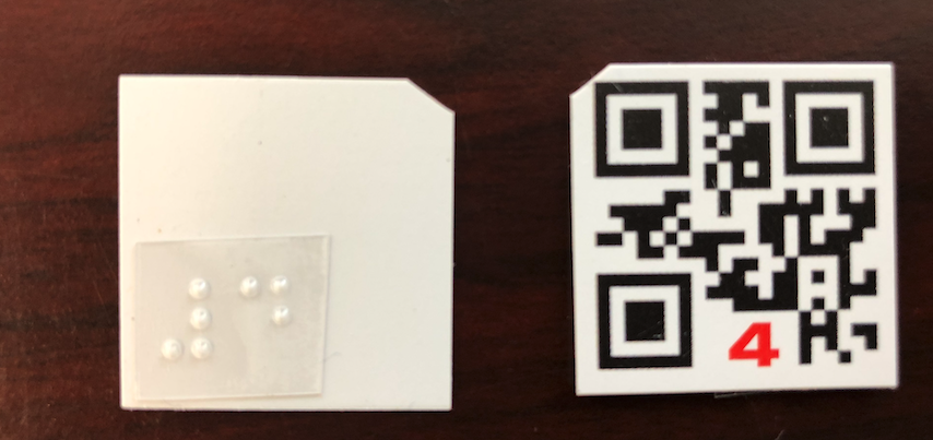 Photo of small QR Square with a number. The top left corner is cut off. The back of the QR square has a braille label.