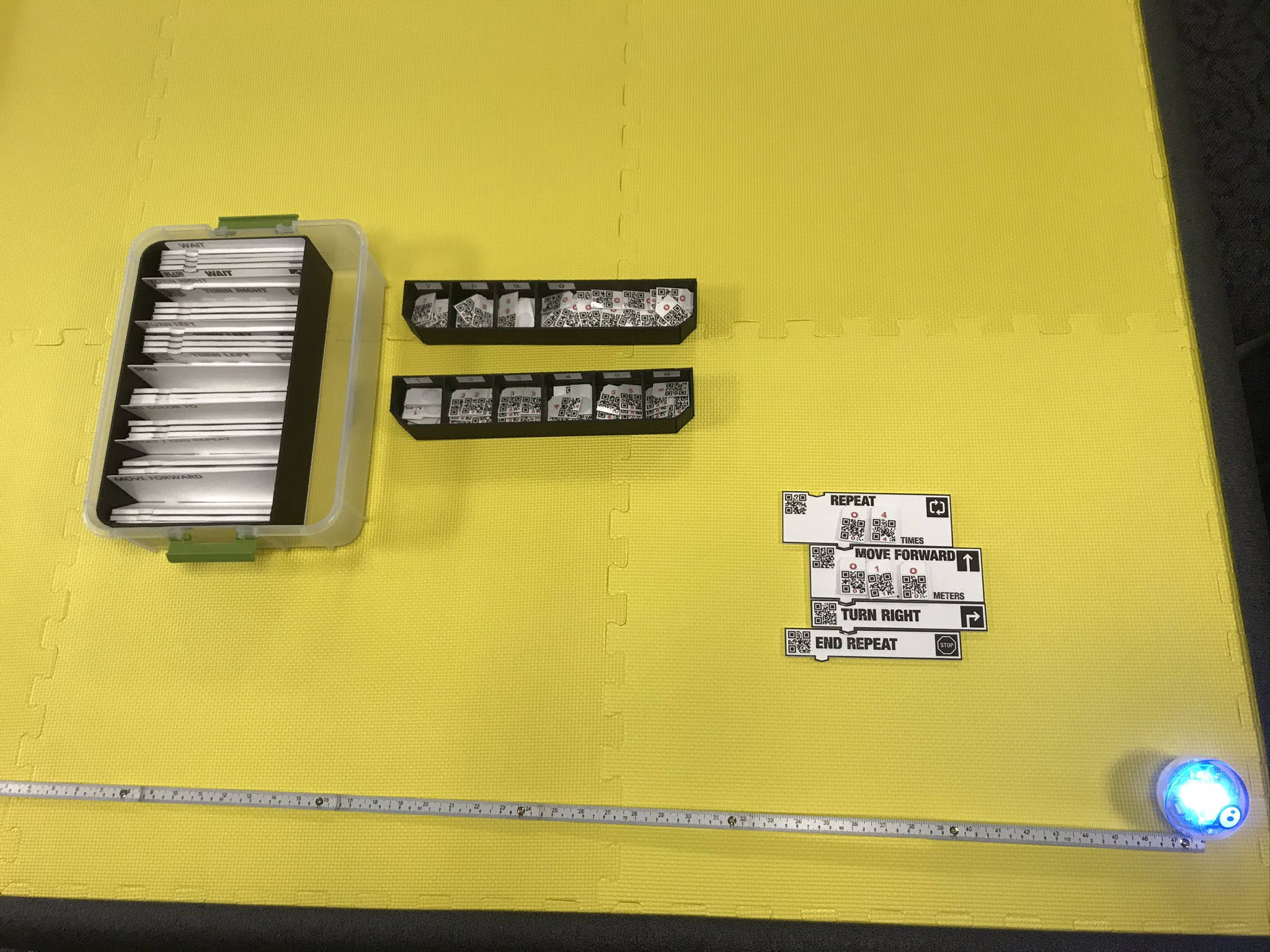 Photo of long table covered with yellow tiled squares, with accessible CodeSnaps cards and organization tubs, SPRK+ and meter stick.