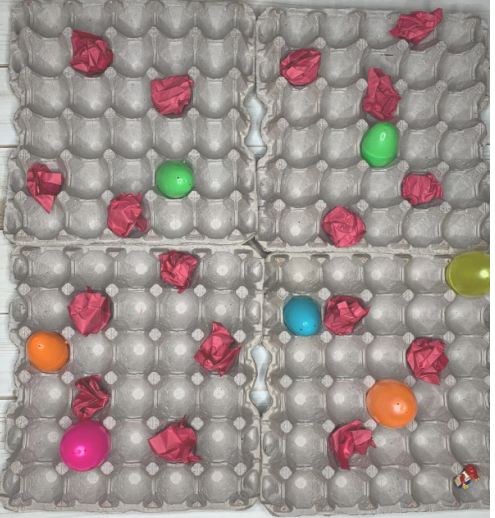 4 30-flat egg carts creating a 12 x 10 grid, with randomly placed 7 plastic Easter eggs and 17 crumpled up red construction paper 'lava rocks'.