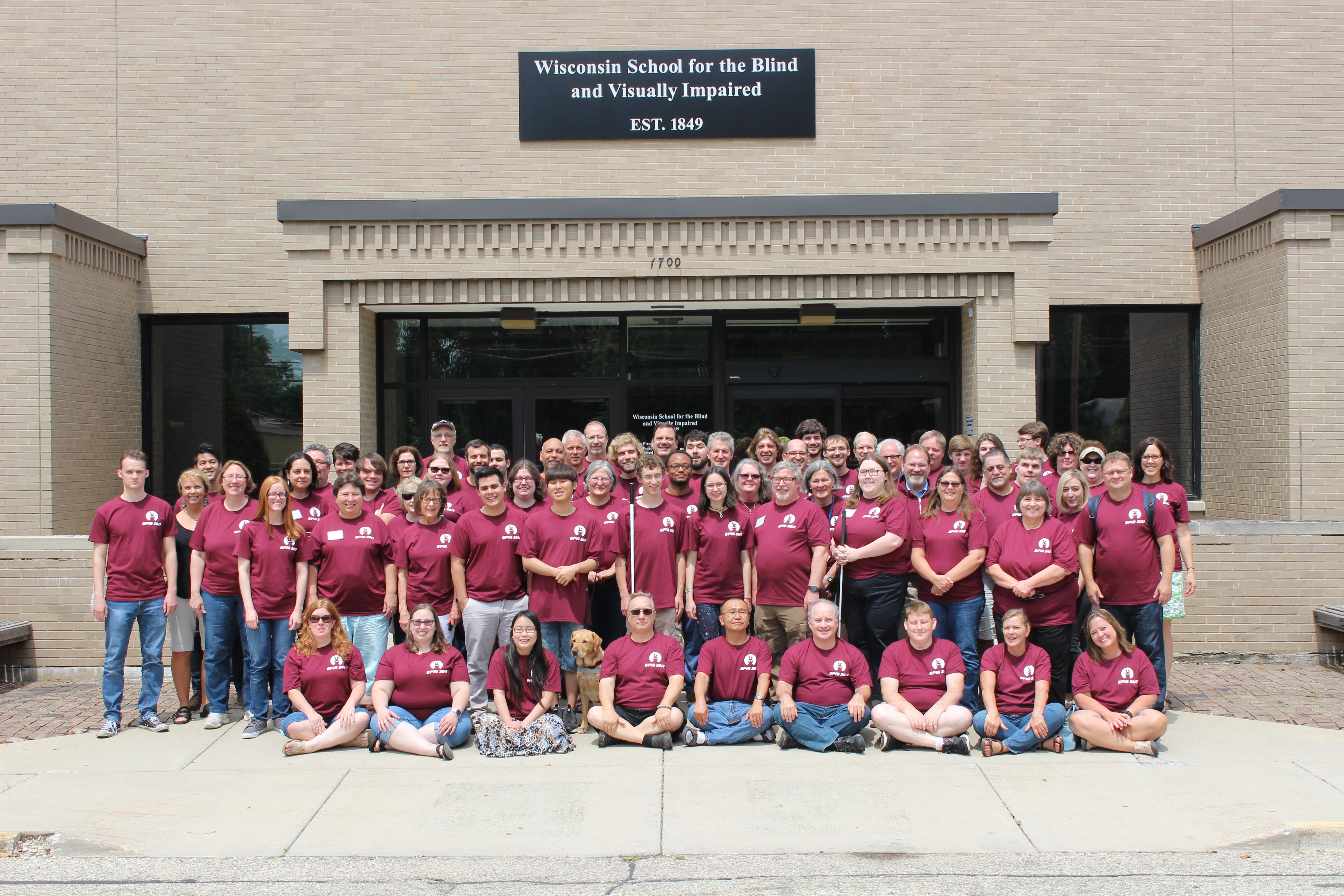 Approximately 75 Participants of the EPIQ conference standing on the steps of the Wisconsin School for the Blind