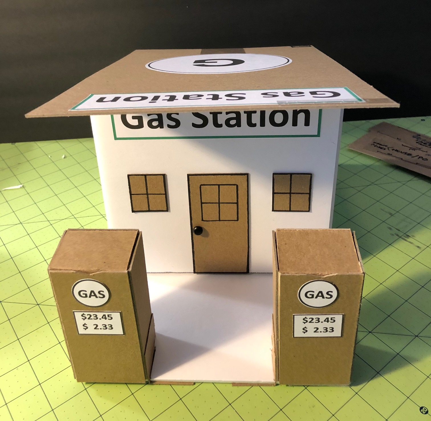 Photo of Small City building front view: Gas station with 2 cardboard gas pumps in front of the building.