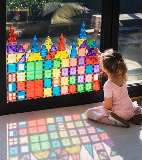 Colorful magnetic tiles (various geometric shapes) being stacked on a glass door by a young girl sitting on the floor. Sun shines throw to create a stained glass window.