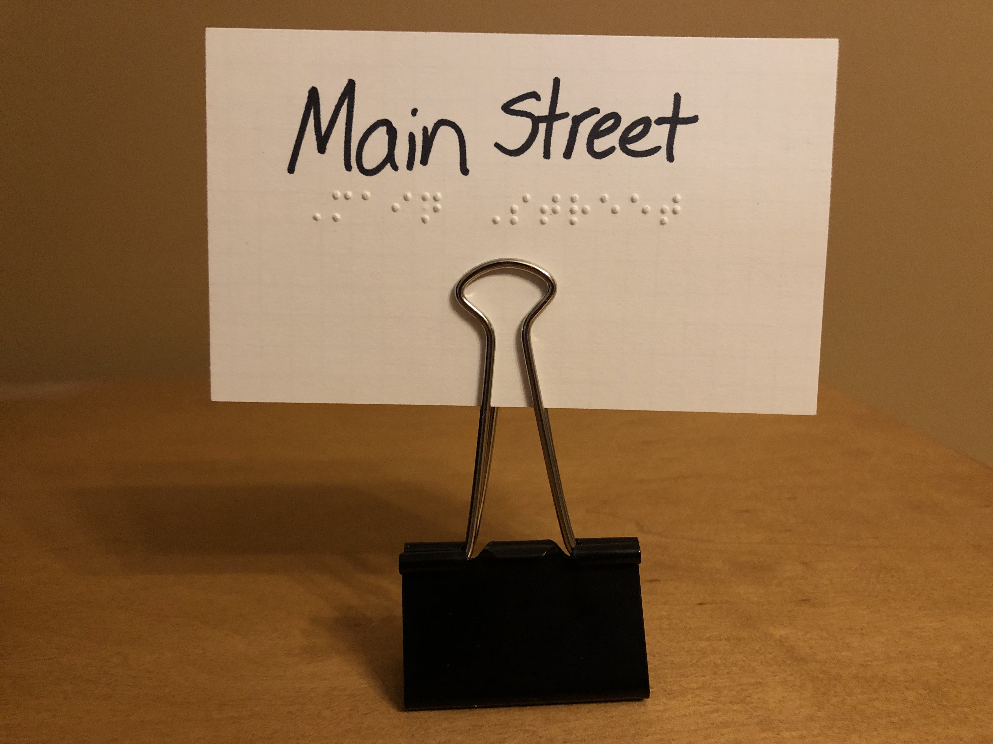 "Index card with ""Main Street"" in print and braille held upright in a large binder clip."