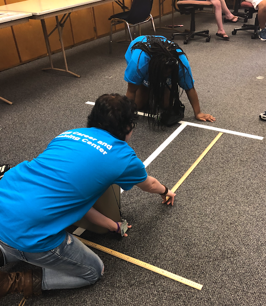 One student holding the yard stick on the Finish line and second student holding the other end.