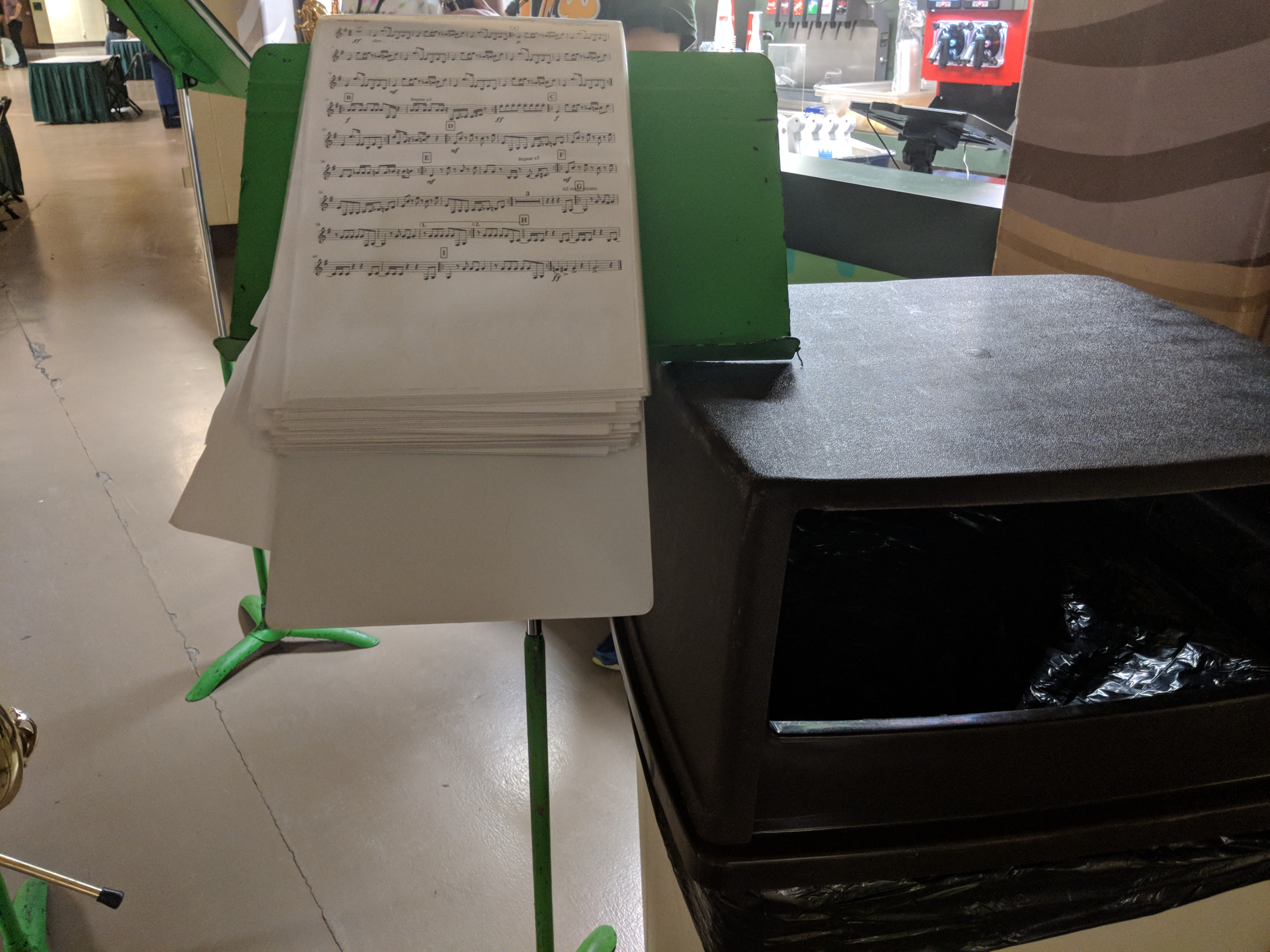 A binder dangling over a music stand supported by a trash can.