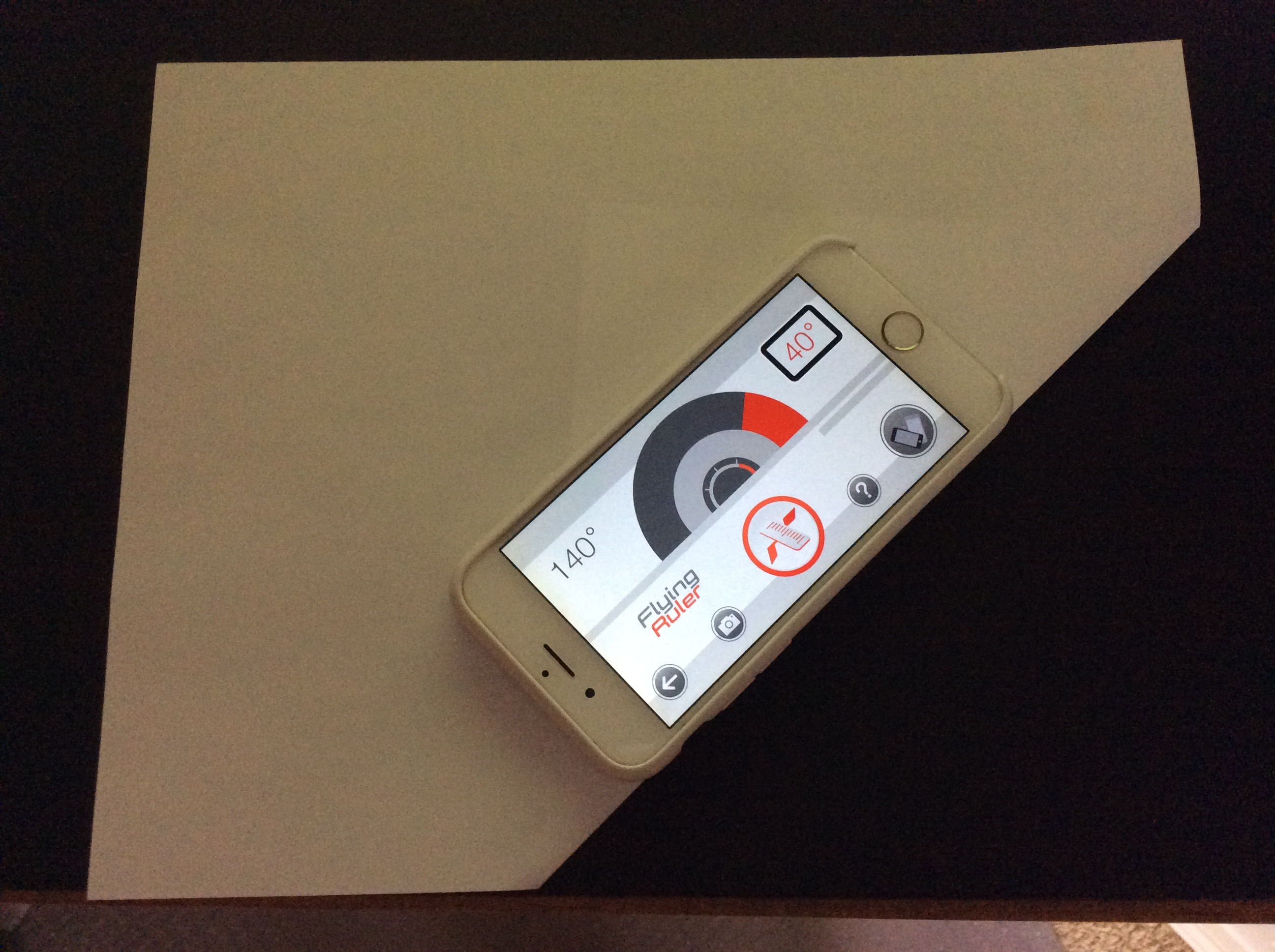 Bottom edge of the phone aligned with folded edge of the paper; Move to Measure app displaying 40 Degrees.