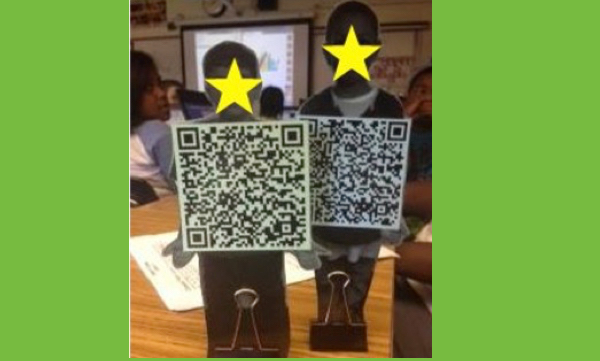 2 QR Kids: cut-out photo of each student with a QR code square for the body standing upright on a desk in a classroom.
