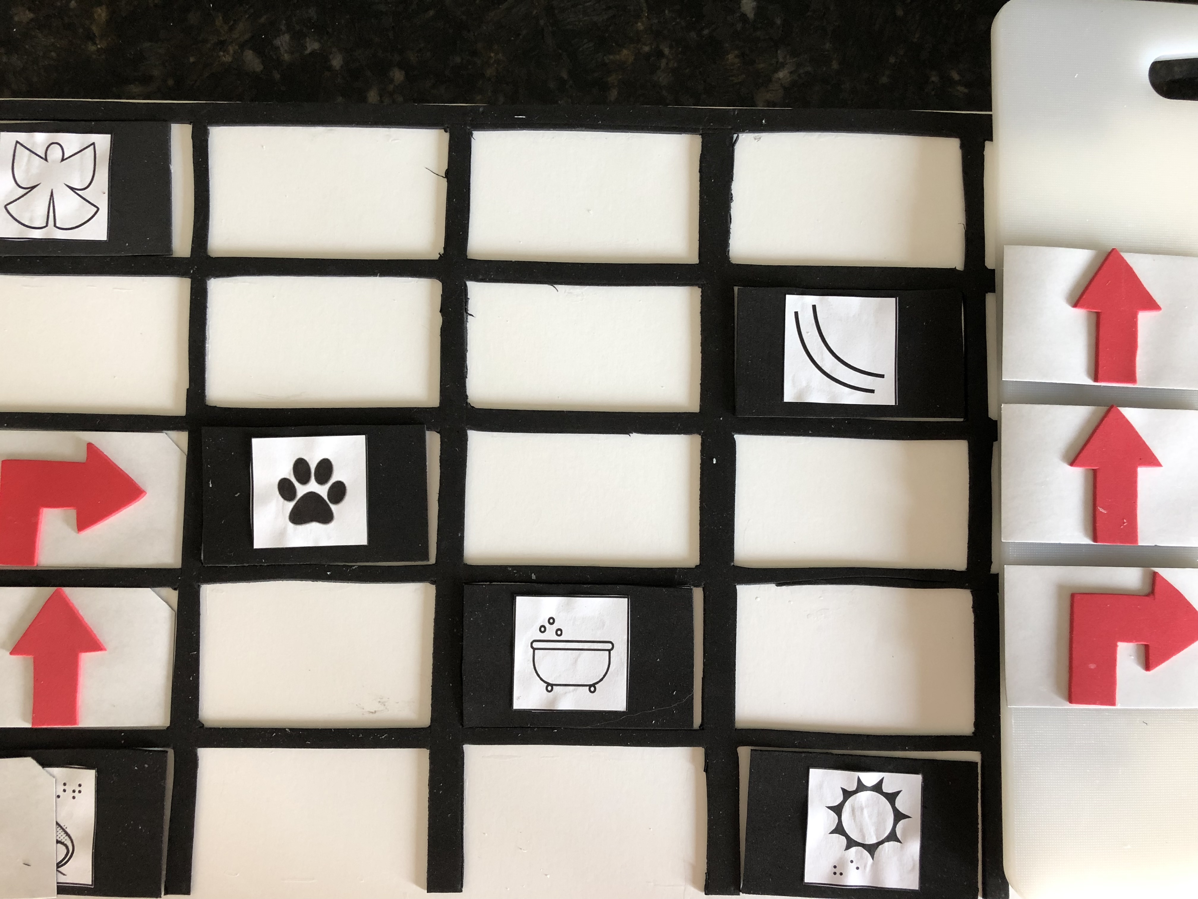 Photo of white foam board, with black tactile grid and Snowy Day cards. A move forward card shares a square with Peter, and additional move forward and turn right cards are placed in empty squares in the path to Tracks.