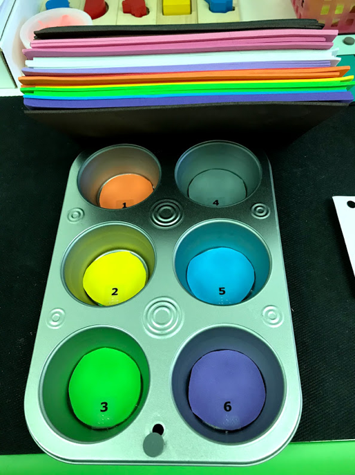Muffin pan with a thin colored foam circle in each department; dot 1 = orange, 2 =  yellow, 3 = green, 4 = grey, 5 = blue, 6 = purple.