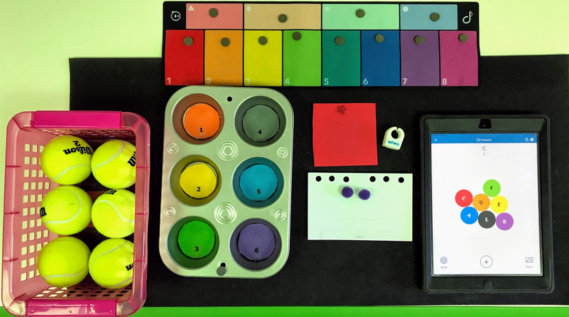 Basket of tennis balls, muffin pan, flashcard, red foam square, Specdrum ring, Specdrums pad and iPad running Specdrum app.
