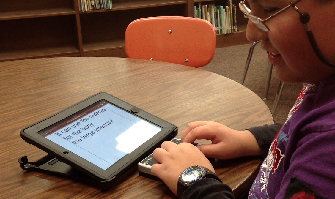 5th grade boy sitting in the library taking notes using his braille display paired on his iPad.