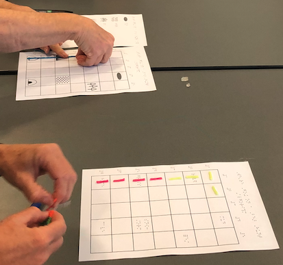PIAF created tactile grids with story images and braille; one person uses a long Wikki stick to show the route while the other person uses a small piece in each square to show the route.